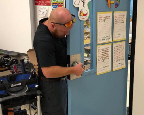 Josh Smith is repairing a door lock at a school for a commercial project